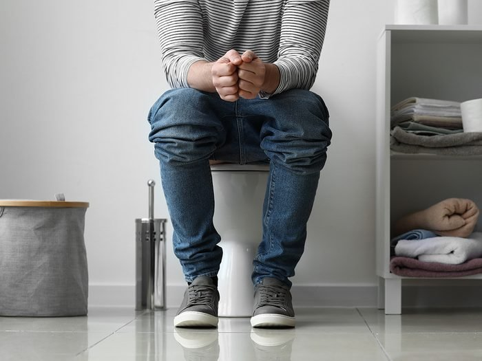 best position to poop - man sitting on toilet