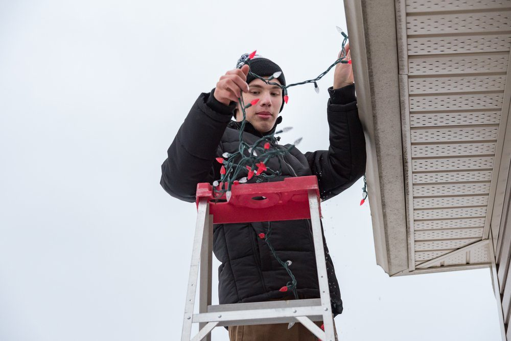 Man hanging Christmas lights during winter from a ladder