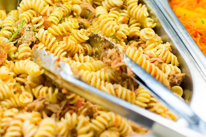 food, catering, self-service and eating concept - close up of pasta and dishes with tongs on metallic tray