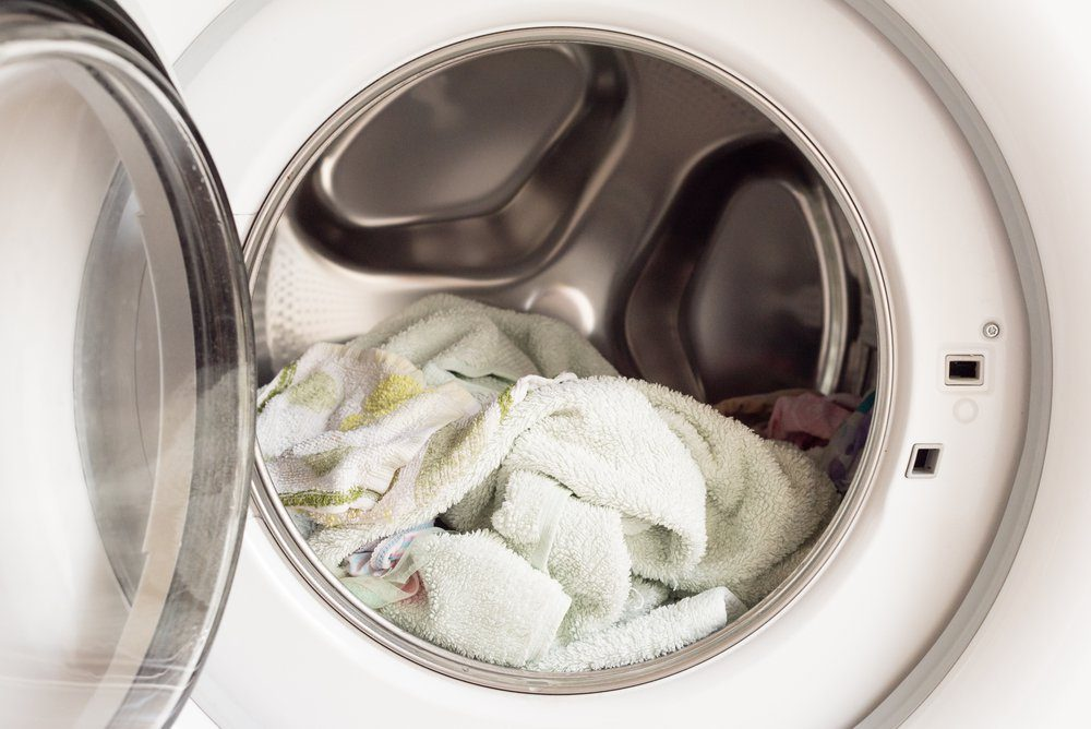 Close up of wet towels in front loading washing machine (selective focus)