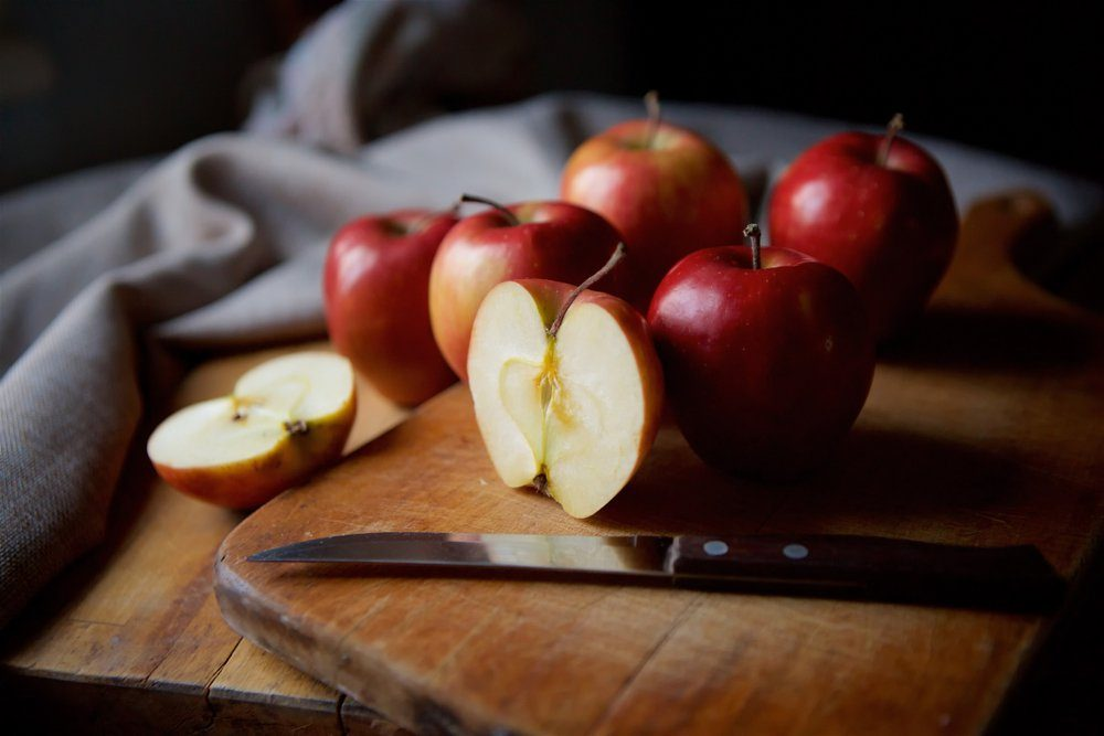 Bright juicy red apples lie on a vintage rustic table. Cut half of the Apple in the foreground.