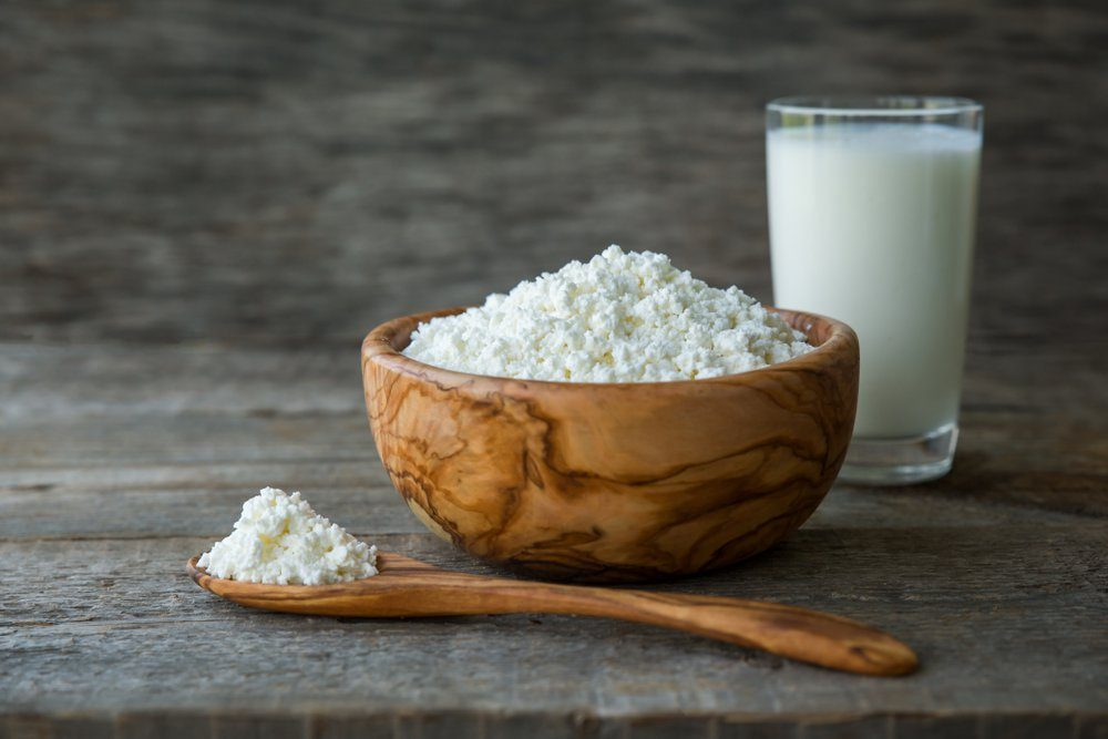 Fresh cottage cheese in a wooden bowl with a spoon with a glass of milk on a wooden old background