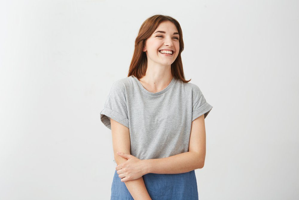 Portrait of sincere young happy cheerful girl smiling laughing over white background.