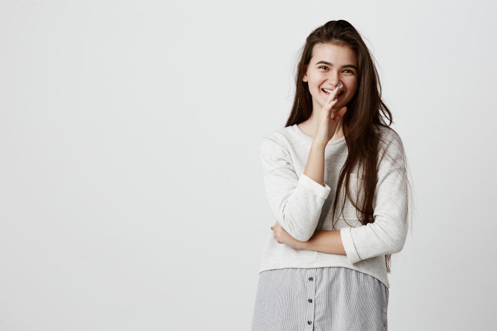 Smiling emotional student girl laughing at joke, posing aganist gray background. Dark-haired brunette young female expressing positive emotions, happily looks at camera.