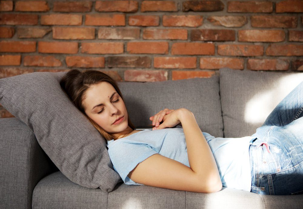 Beautiful young woman is sleeping on couch.