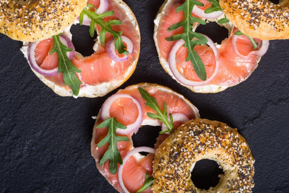 Homemade bagels with salmon , cream cheese and onion .