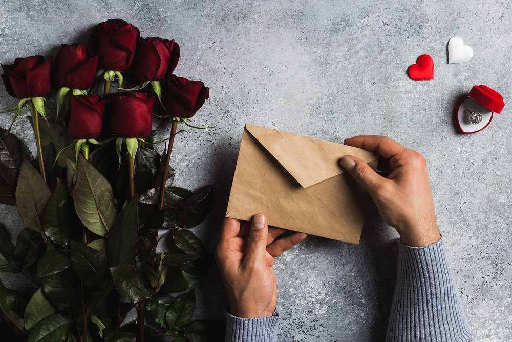 Valentines day man hand holding envelope love letter with greeting card mothers day red rose gift surprise on grey background with copyspace. Love flower gift for woman romantic holiday birthday