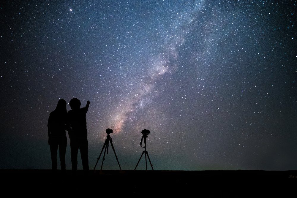 Couple photographer standing near the camera and looking milky way and stars on the sky at night.silhouette style.this photo may have a few noise.