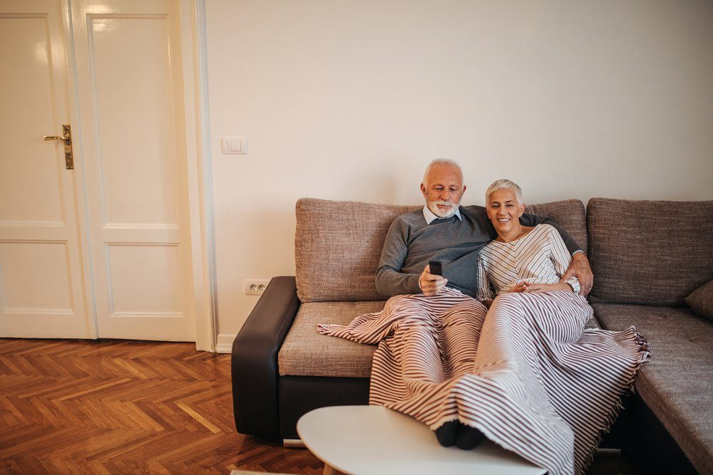 A senior couple lying on their couch with their legs up and watching tv.