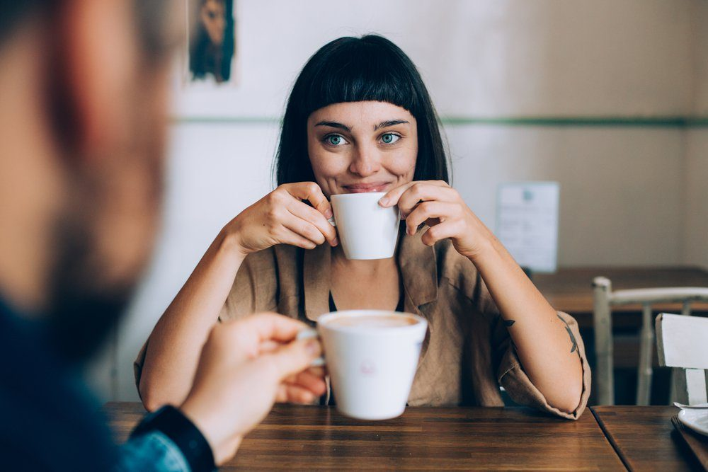 Happy romantic couple on date, drink warm coffee with milk, she looks lovingly at her boyfriend or partner, smiles and spark in her eyes. early morning family routine