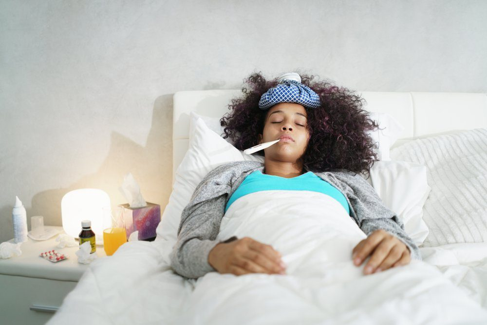 Sick african american girl with flu in bedroom at home. Ill young black woman with cold, lying in bed and holding a thermometer in her mouth.