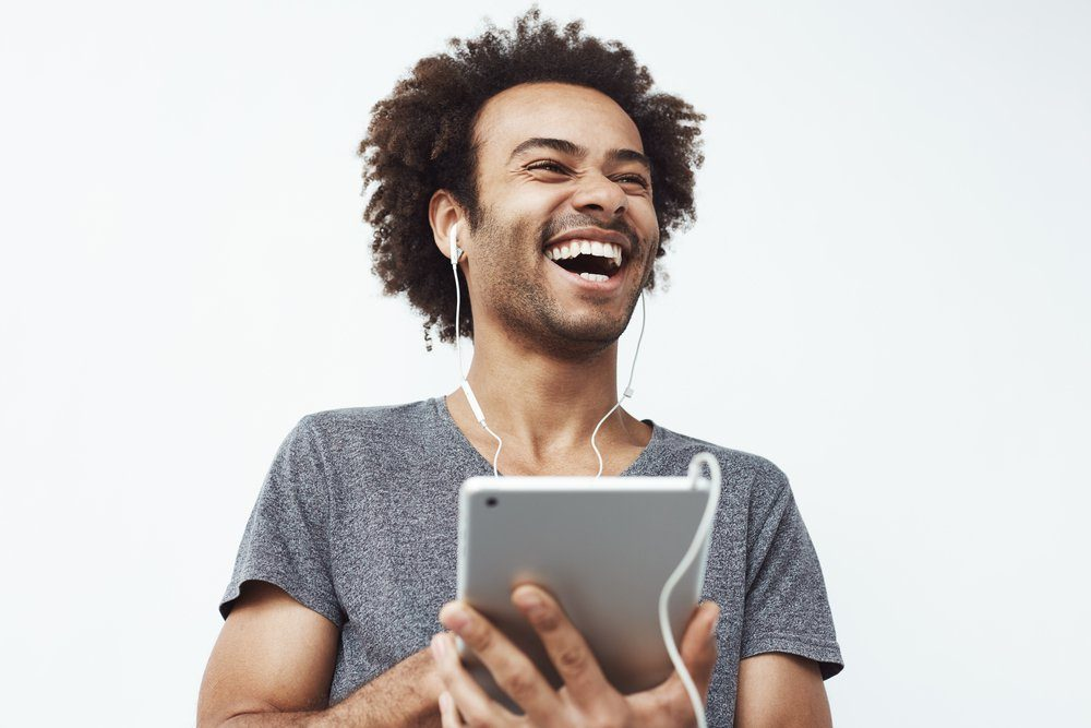 Portrait of cheerful happy african man in headphones laughing holding tablet talking or watching and enjoying a comedy show or browsing over white background.