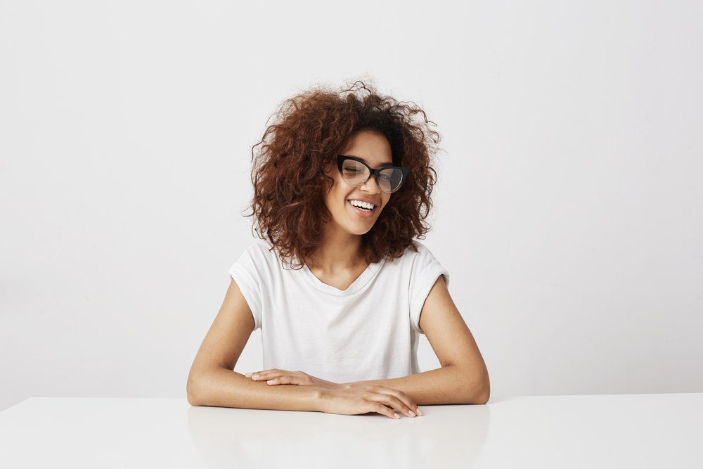Beautiful african girl in glasses laughing sitting over white background. Copy space.