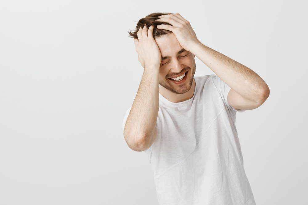 Man remembering funny moment while talking with old friend laughing out loud from joy and happiness holding hands on head closing eyes and looking down feeling upbeat and carefree over gray wall