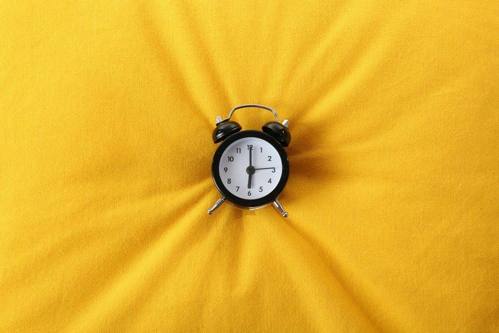 Alarm clock on pillow, close up