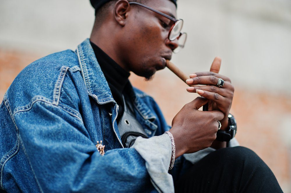 African american man in jeans jacket, beret and eyeglasses, lights a cigar.