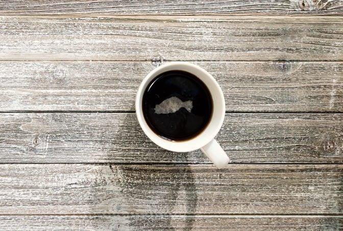 Coffee mug on a wooden desk overhead view