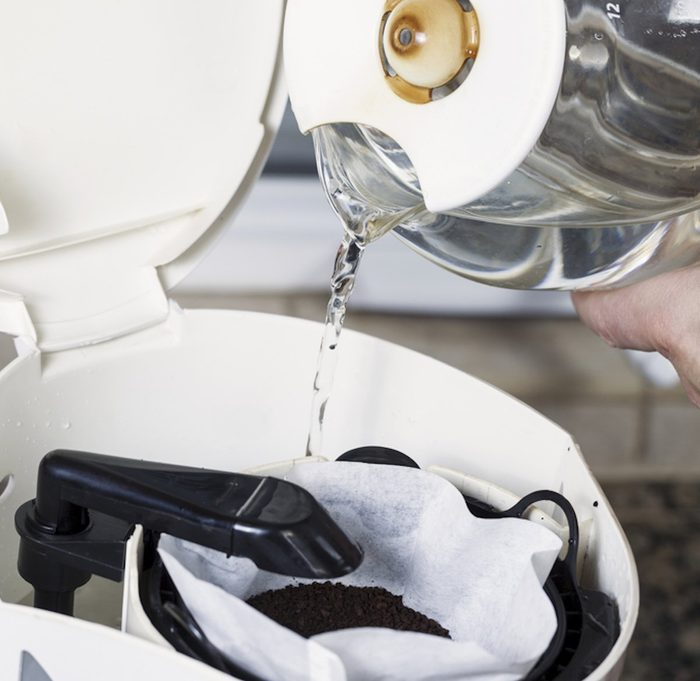 Horizontal photo of male hand pouring water, from coffee pot, into coffee maker with fresh coffee grounds in white bleached coffee filter with stone kitchen counter top ; Shutterstock ID 156211847