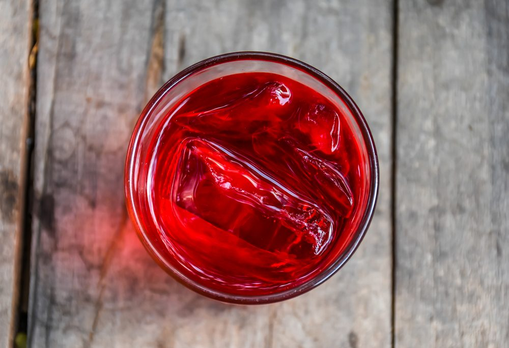Refreshing Red Soda with Ice on a wooden background