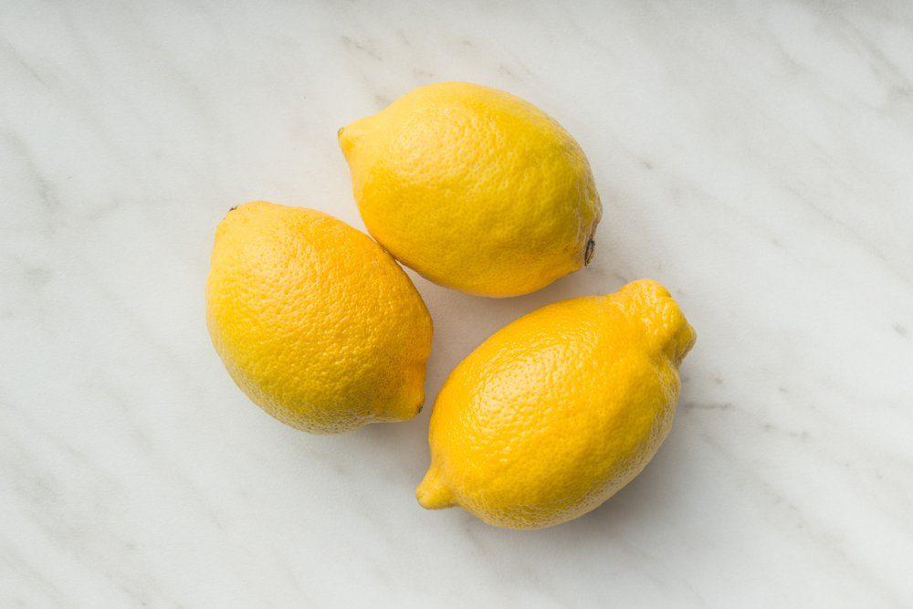 Three yellow lemons on table. Top view.