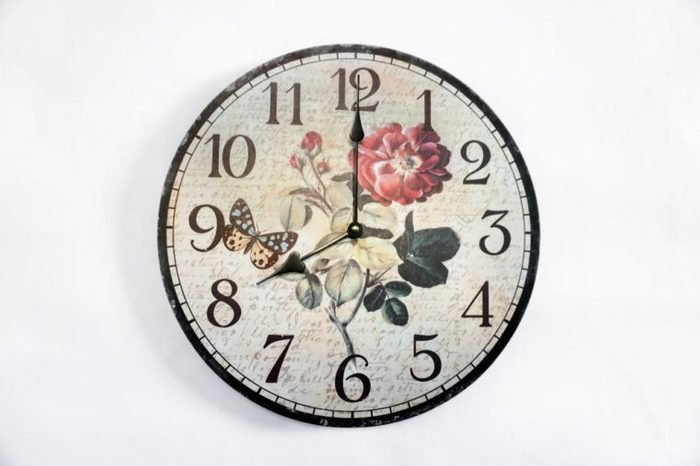 Vintage clock hanging on white wall shows eight o'clock