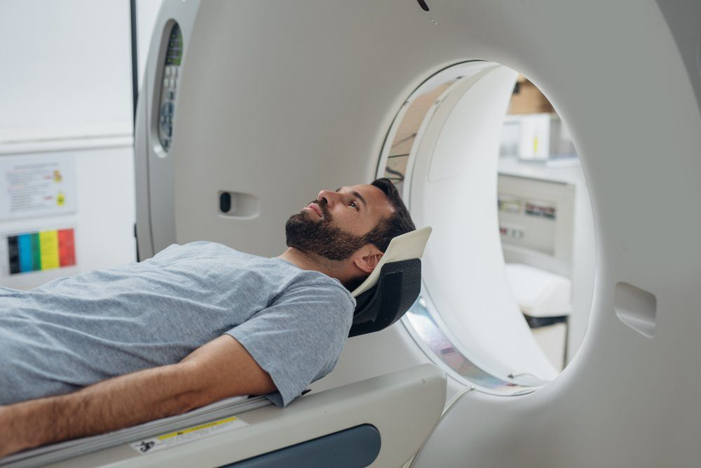 Patient lying on the TC scanner bed waiting to be scanned.