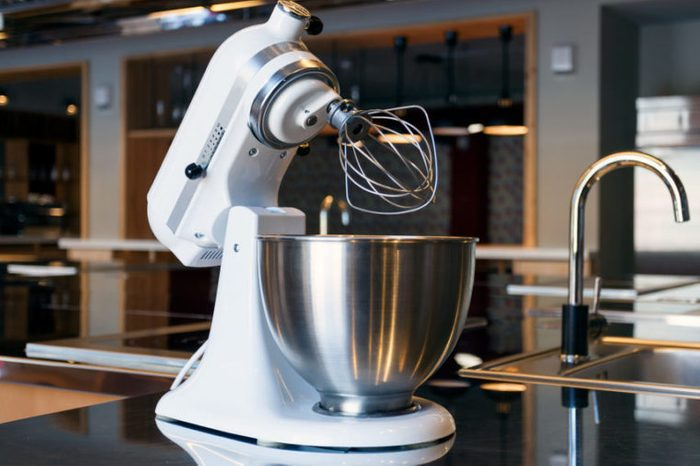 A beautiful white mixer with a metal cup stands in the modern kitchen