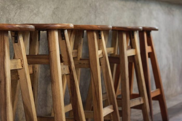 A high chair made of wood laid in front of a table made of mortar is like a bar.