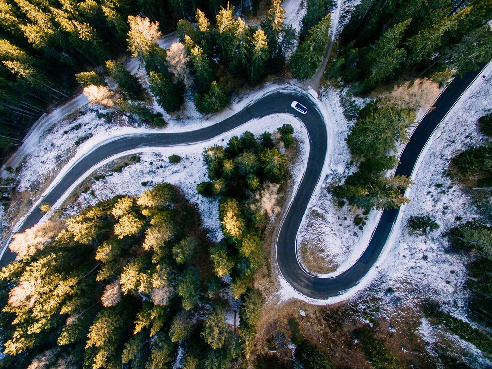 Aerial view of snowy forest with a road, Dolomites, Italy