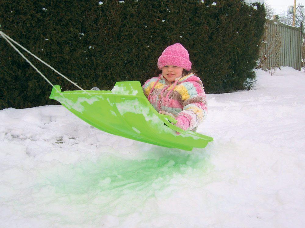 Little girl snow sledding