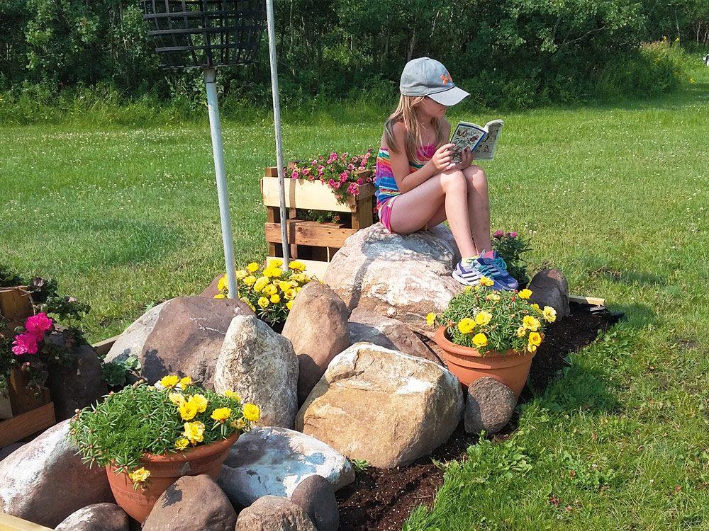 Little girl reading a book in her garden