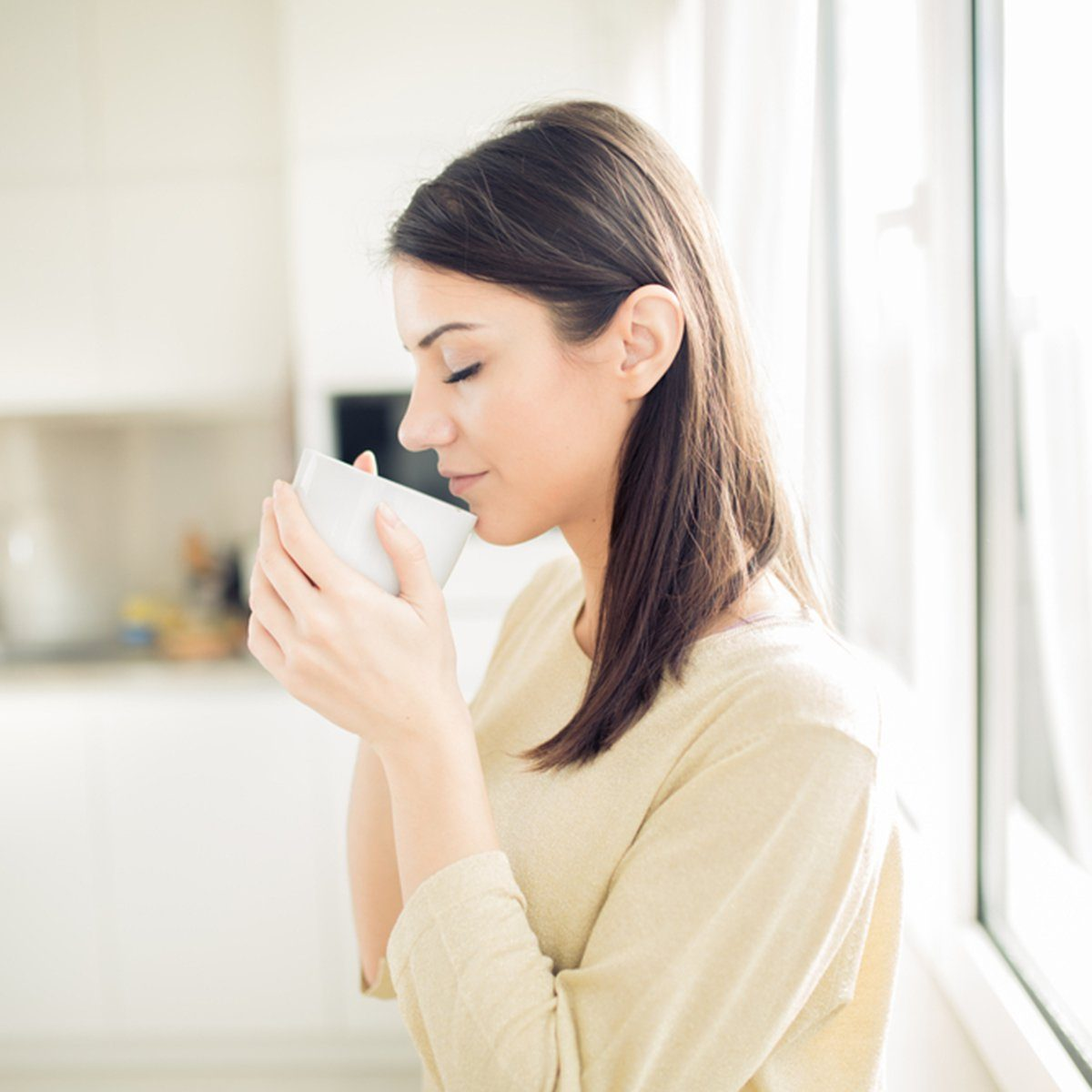 Modern working woman lifestyle-drinking coffee or tea in the morning in the kitchen,starting your day.