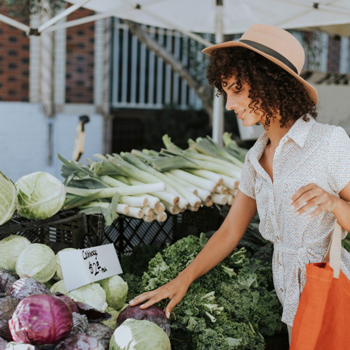 Beautiful woman buying vegetables at a farmers market