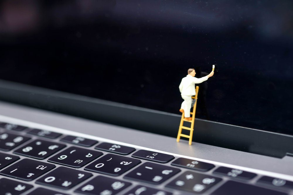 Miniature people : worker with ladder and painting in front of screen laptop.