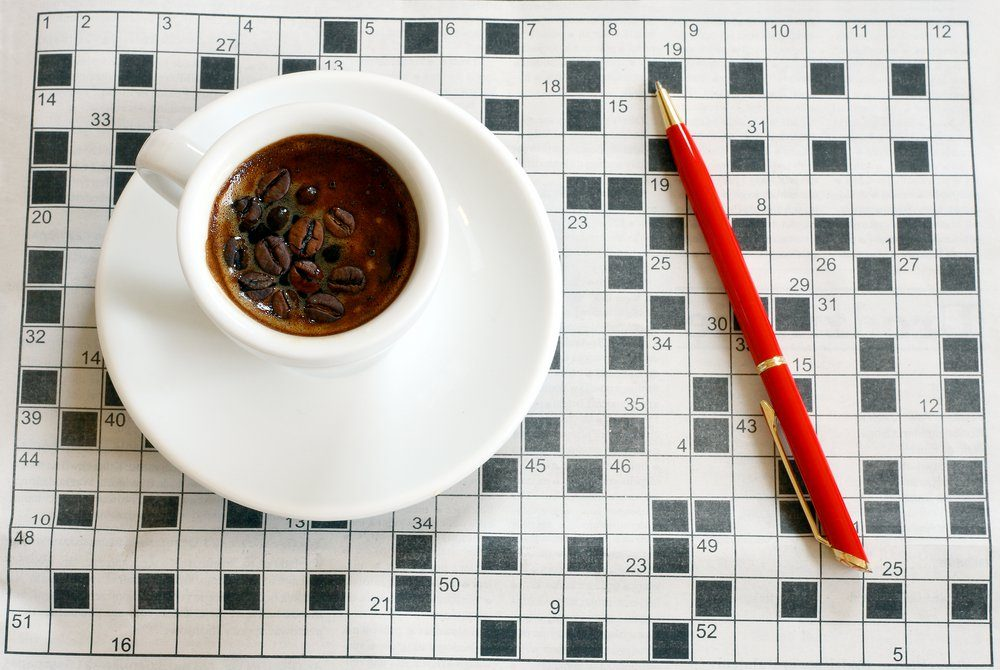 a cup of coffee with crossword in background