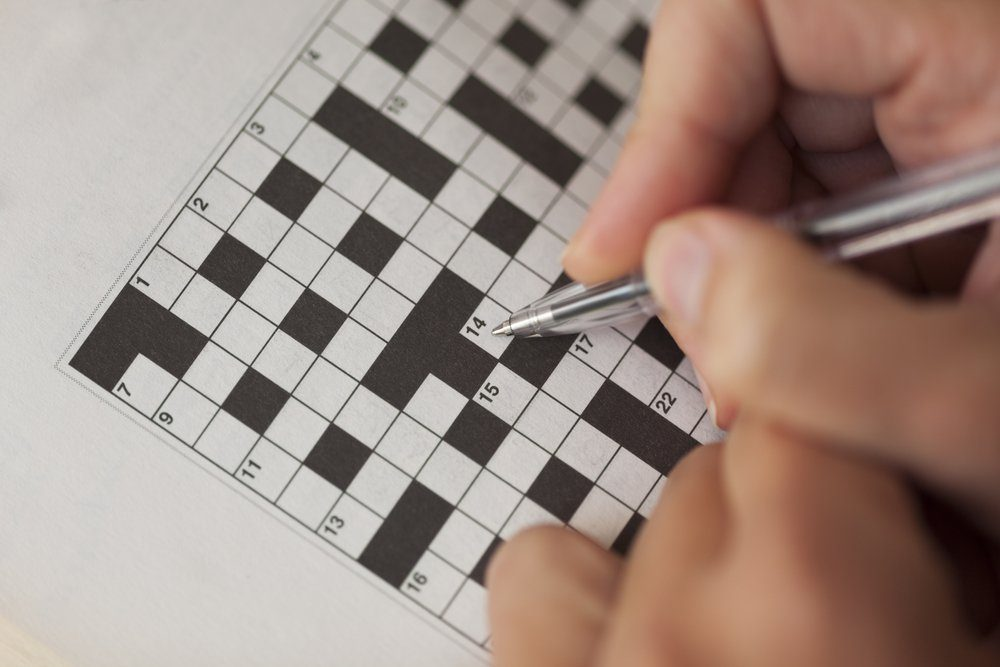 Woman's hand with ballpoint pen is filling crossword puzzle.