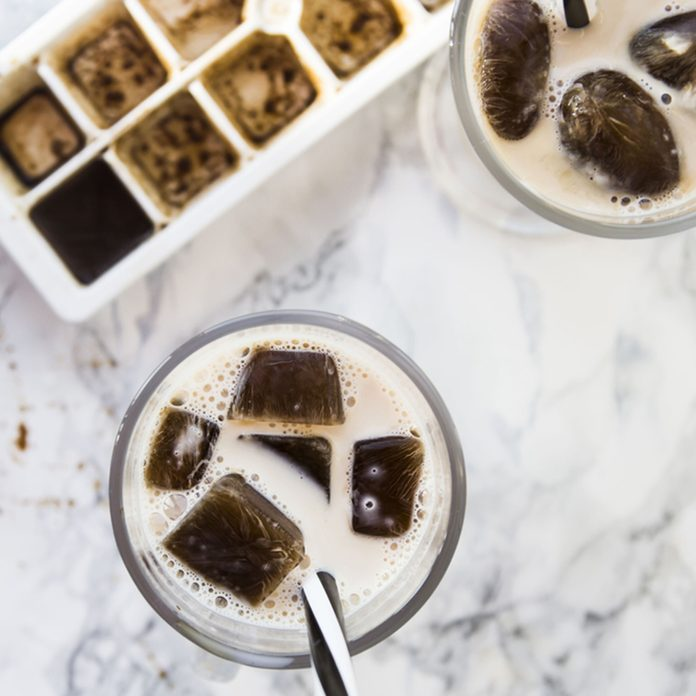 frozen coffee cubes with milk - cocktails on marble table; Shutterstock ID 565170853