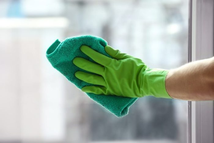 Hand of young man cleaning window in office