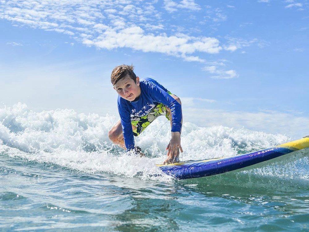 Teenage boy surfing at Los Cerritos Beach in Todos Santos