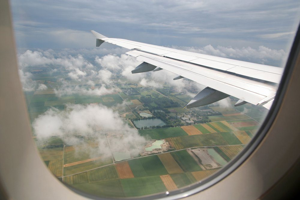 The view form inside the window of an airplane while approaching for landing at the airport of Munich, Germany