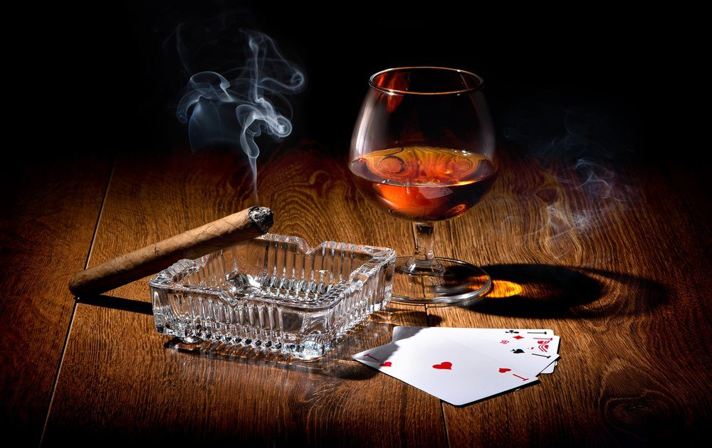 Playing cards near wineglass of whiskey and cigar