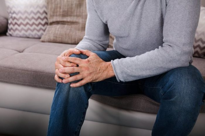 Man Suffering From Knee Pain Sitting On Sofa
