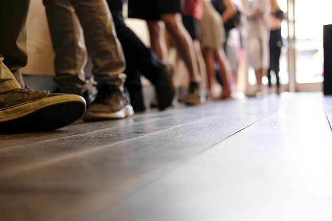 Medium shot of line of people's legs