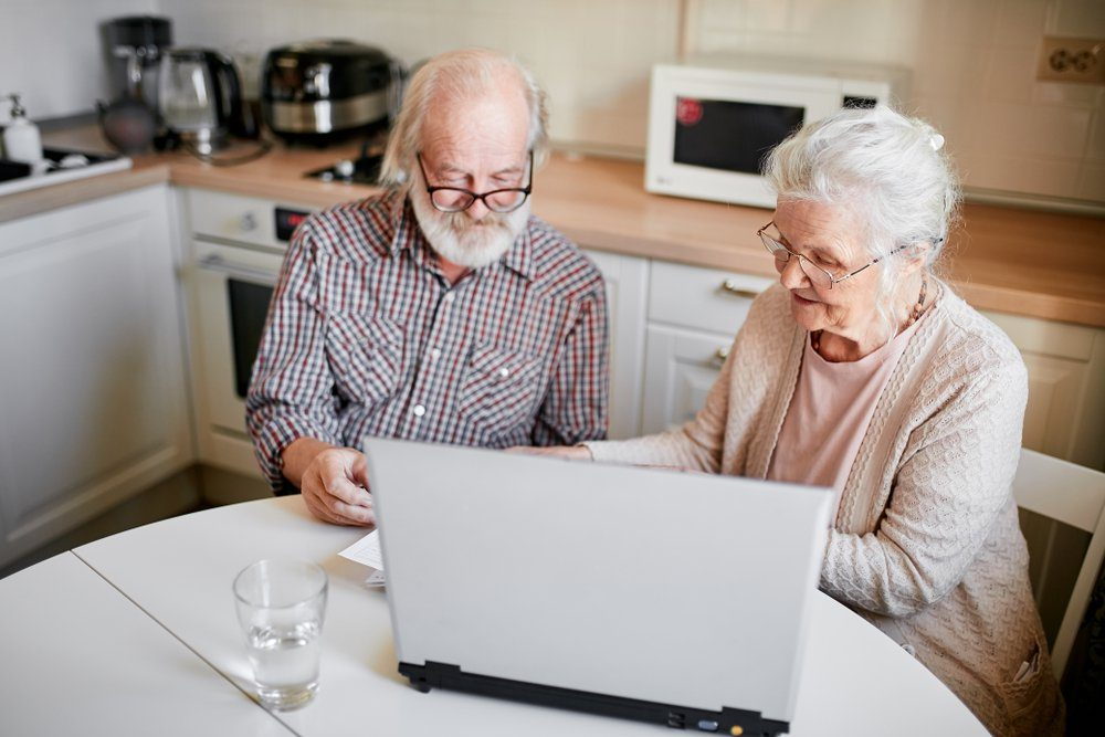 Senior couple at home kitchen using laptop, writing email to their foreign far-away friends, one of the pensioners holding document, another typing on computer keyboard. Close up.