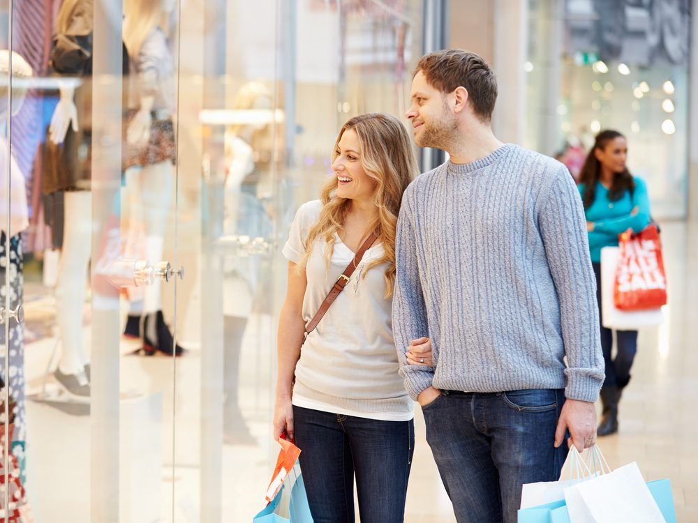 Happy couple carrying shopping bags in shopping mall