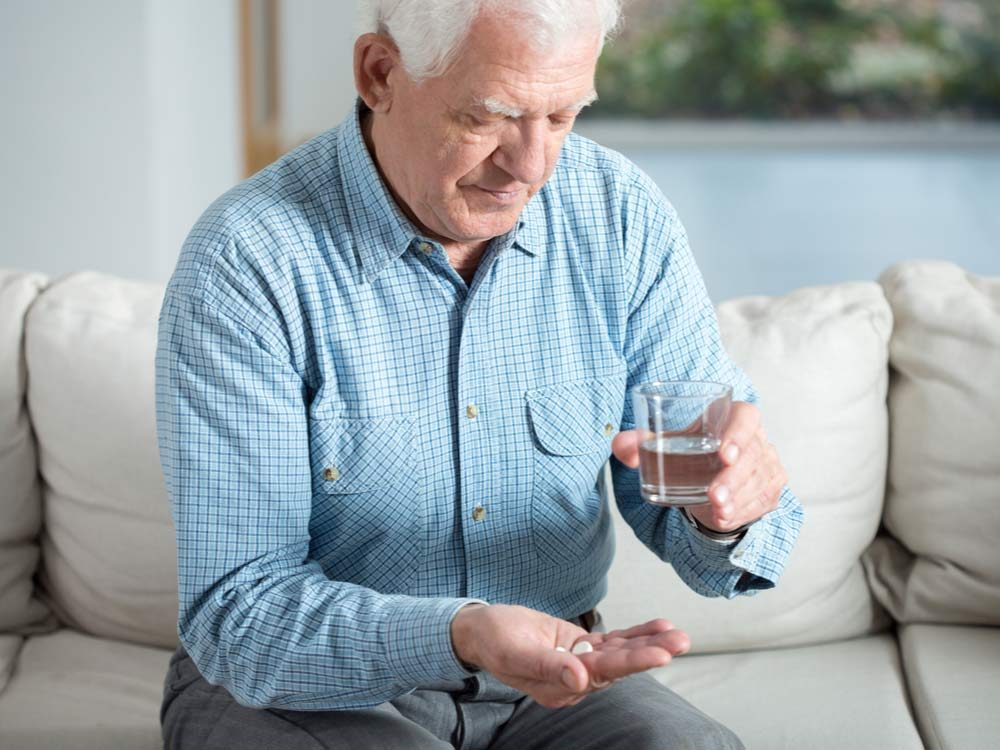 Elderly man taking a Tylenol