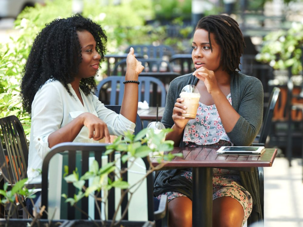Two female friends having coffee on patio
