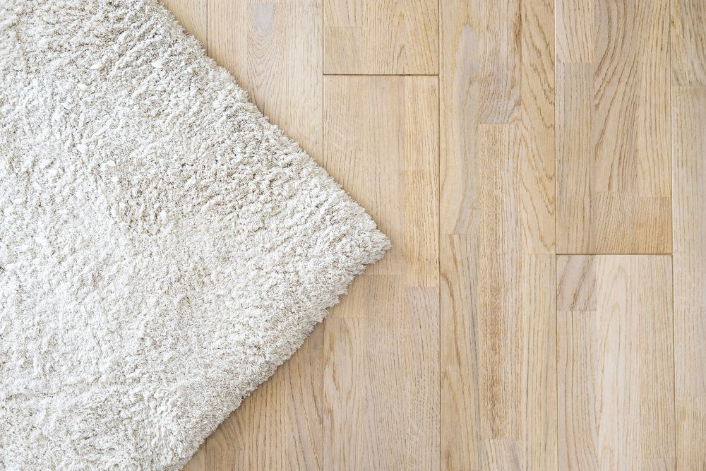 Laminate parquete floor. Light wooden texture. Beige soft carpet. Warm interior design