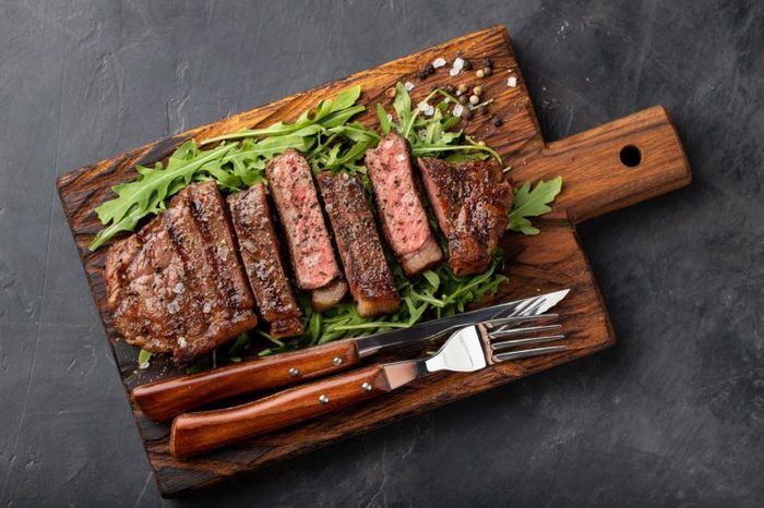 Closeup ready to eat steak new York beef breeds of black Angus with herbs, garlic and butter on a wooden Board. The finished dish for dinner on a dark stone background. Top view