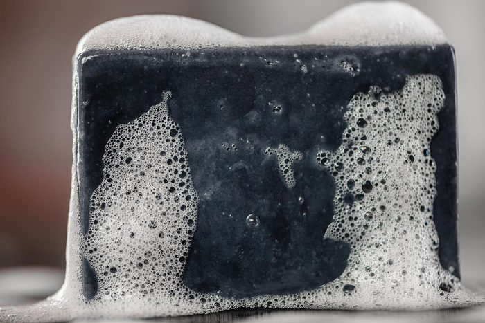 black charcoal carbon soap on black background with soap bublles foam